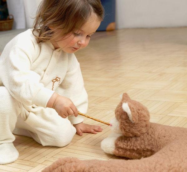 Kind im Wollschlafanzug spielt mit Plüschkatze